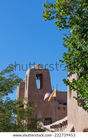 A historic southwestern building with a bell tower and flags surrounded by trees and a blue sky. - stock photo