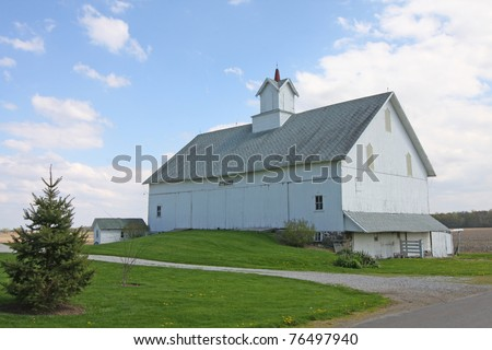 A historic White Barn with a cupola - stock photo