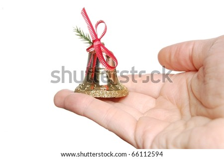 A Holiday Bell, Trimmed with Red Ribbon Being Held in the Palm of a Woman's Hand - stock photo