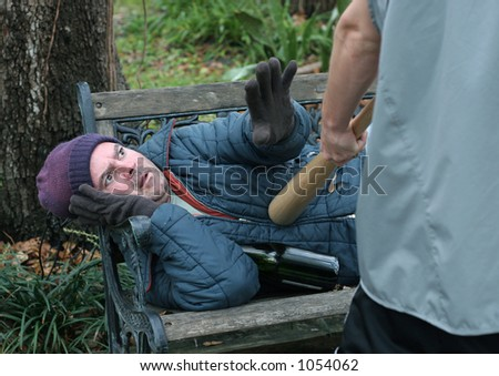 A homeless man defending himself against a teen with a bat. - stock photo