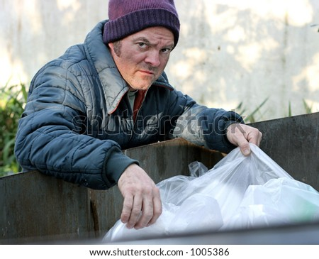 A homeless man rooting in a dumpster for food. - stock photo