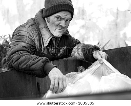 A homeless man rooting in a dumpster for food. Black and White. - stock photo