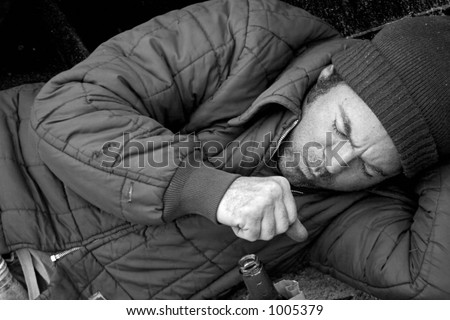 A homeless man sleeping on the streets and coughing. B & W and film grain effect added for drama. - stock photo