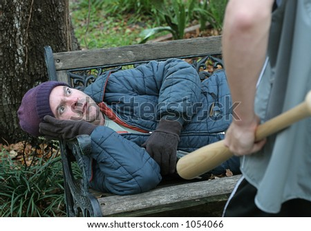 A homeless man, terrified of being the victim of a hate crime. - stock photo