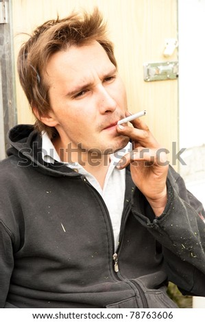 a homeless poor young guy smoking - stock photo