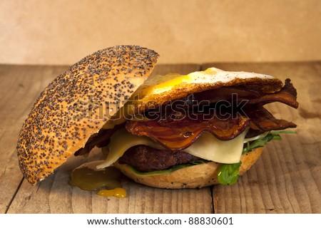 A homemade egg, bacon and cheese burger on an old wooden table. Egg, bacon and cheese burger. - stock photo