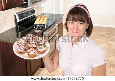 A homemaker shows off her decorated cupcakes with pink icing and candy sprinkles. - stock photo