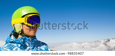 A horizontal panorama with a portrait of a female snowboarder wearing a helmet with a bright reflection in the glasses on the background of high snow-capped Alps in Grindelwald, Swiss - stock photo