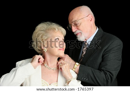 A horizontal view of a senior man fastening his wife's necklace as they prepare for an evening out. - stock photo