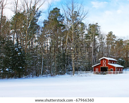 A Horse barn in a field in the woods covered in snow after a snowstorm with room for your text. - stock photo