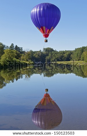 A hot air balloon and its reflection over a clear blue pond. - stock photo