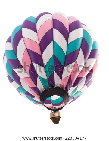 A hot air balloon in colors of pink, purple, green, and white floating above and isolated on white. - stock photo