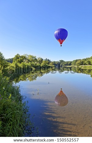 A hot air balloon rises into a blue sky over a clear pond with reflection. - stock photo