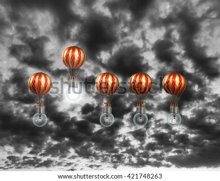 A hot air balloons powered by a lit lightbulb, rising above the others against a surreal evening sky for the concept of competitive advantage from a bright idea.  - stock photo