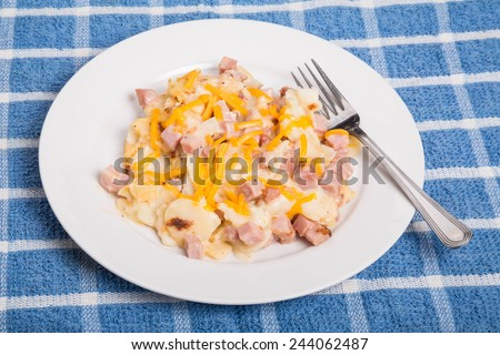 A hot casserole of ham and potatoes with grated cheddar cheese - stock photo