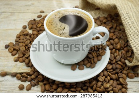 A Hot Cup of Strong and Flavored Coffee among Light Roasted Coffee Beans on a Wooden Table - stock photo
