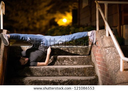 A hot female model doing a stunning split upside down on the stairs. Her hear on the floor and feet touching the side walls of stairs. - stock photo