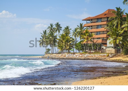 A hotel at the Hikkaduwa Beach on a split which project into the shining blue Indian Ocean, and the beach by falling tide. - stock photo