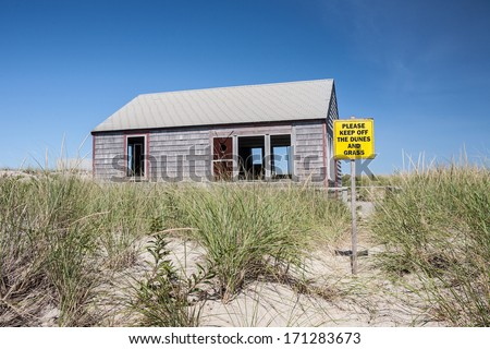 A house built on an eroding beach on Cape Cod, Massachusetts is soon to be demolished as strong storms and sea level rise due to climate change threatens the coastline. - stock photo