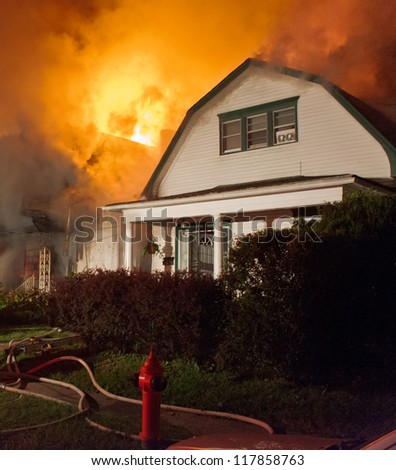 A house fire with heavy smoke and flame next to a house now threatened by the fire. - stock photo