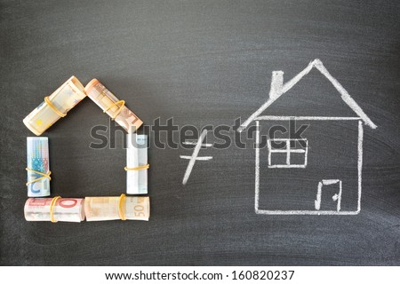 A house made of rolled up Euro banknotes next to a hand drawn house of chalk over a blackboard. - stock photo