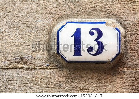 A house number thirteen (13) on a wall in Lucca, Italy - stock photo