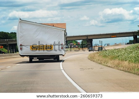 A house trailer (mobile home) being transported along Interstate Highway.  Half of double wide modular home. - stock photo
