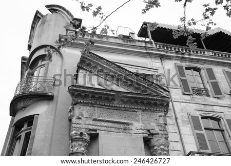 A house with Roman portico and columns in Arles (Provence, France). Aged photo. Black and white. - stock photo