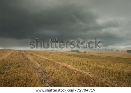 A huge and terrible storm cloud over the fields after harvest - stock photo