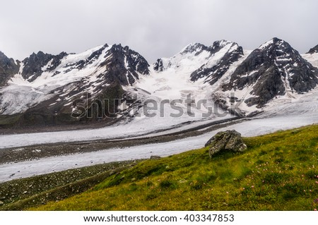 A huge Bartuy Glacier in the Caucasus Mountains, in cloudy weather - stock photo