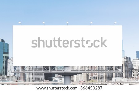A huge blank billboard in the city centre at daytime. Front view. Concept of outdoor advertising. 3D rendering - stock photo