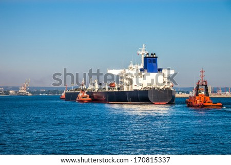 A huge oil tanker and tugboats at work.  - stock photo