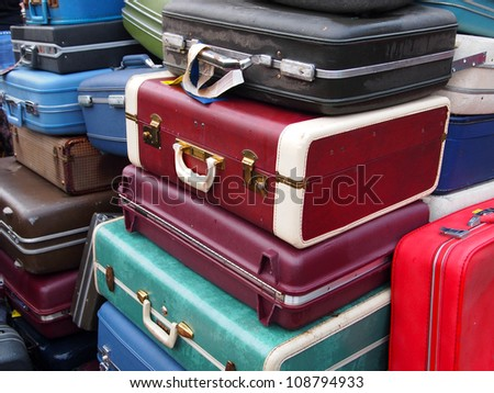 A huge pile of old suitcases in many colors piled up together. - stock photo