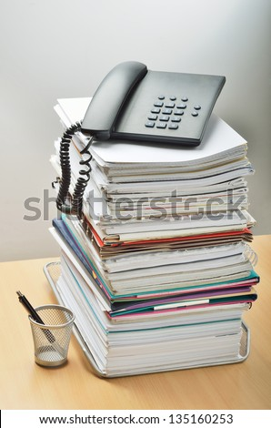 A huge pile of paperwork on a desk and a phone above it - stock photo