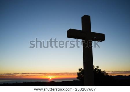 A huge stone cross in the sunrise light - stock photo