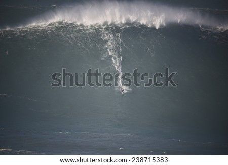 A huge wave breaking with a surfer in Nazare, Portugal.  - stock photo