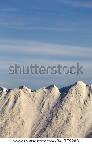 A huge white mountain of road salt with blue sky and birds flying by behind it. - stock photo