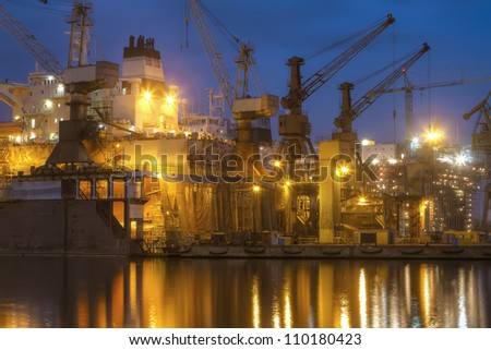 A hull of a ship is being renovated in a dry dock - stock photo