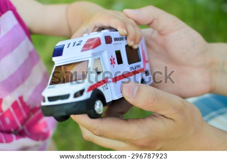 A human hand giving a toy car with the word emergency over it it to a child demonstrating concept of lifesaving - stock photo