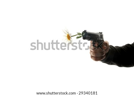 a human hand holds a hand gun with a white daisy in the barrel representing peace and love concepts with room for text - stock photo