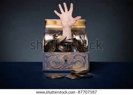 A human hand protruding from the open chest with money. - stock photo