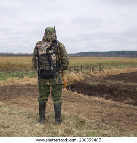 A hunter with a gun and a backpack standing on the edge of the swamp - stock photo