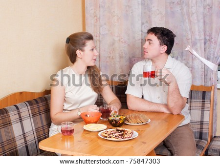 A husband and wife at the table drinking tea in the kitchen - stock photo