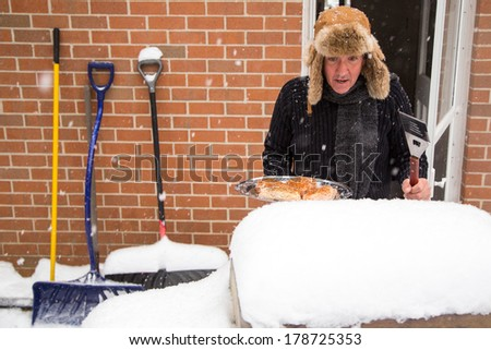 A husband heads out the back door with a tray of chicken and stares in disbelief at his barbecue buried in snow. - stock photo