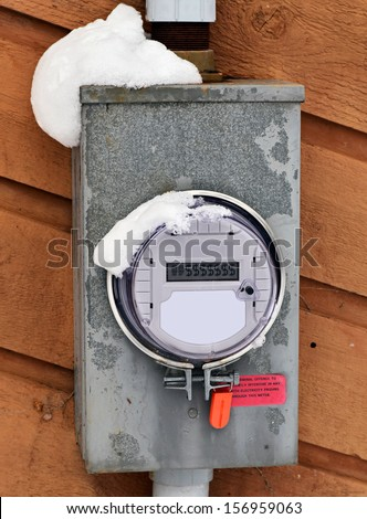 A Hydro Electric Smart Meter covered with snow displaying $ dollar signs on the readout.  Room for copy space or text. - stock photo