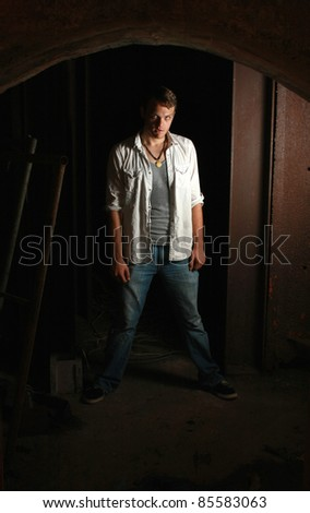 A intense man standing in the dark - stock photo