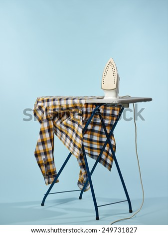 A iron and checkered shirt on the ironing board, light blue background - stock photo