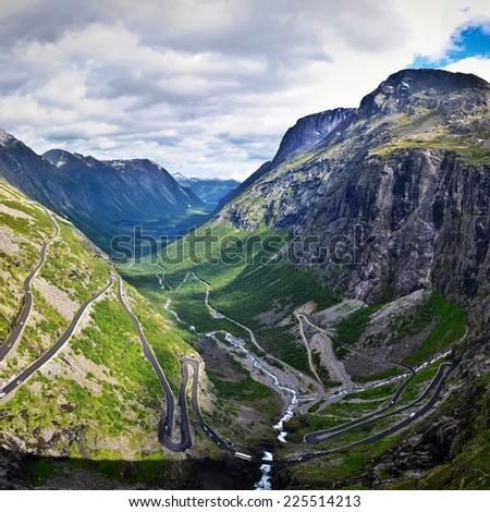 A jagged road cutting through a mountain range. - stock photo