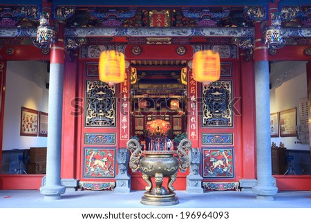 A Japanese building with blue pillars and hanging lanterns. - stock photo