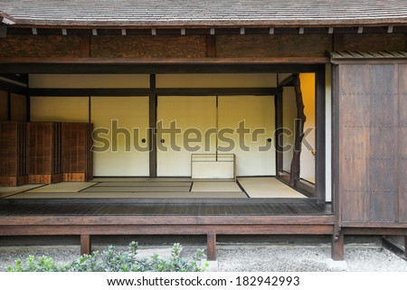 A japanese home made of wood, with the walls open into the garden. - stock photo